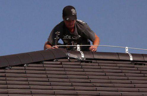 Электрик устанавливает молниезащиту на крыше