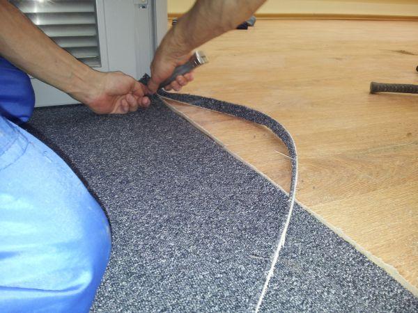Мастер производит монтаж ковролина на пол