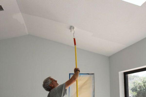 Мастер красит потолок валиком