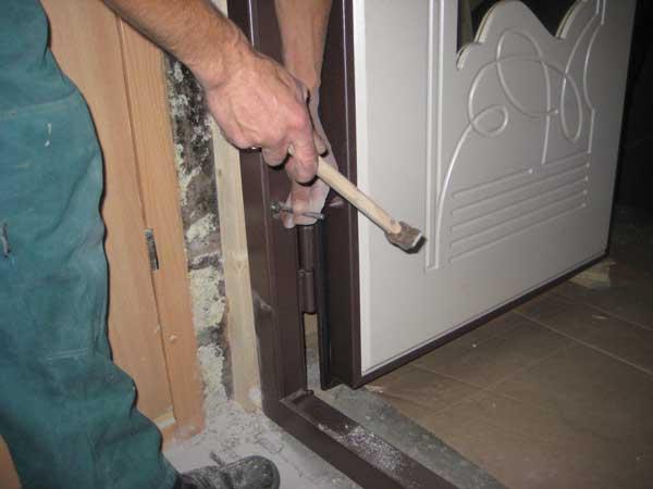 Мастер ставит входную дверь в доме